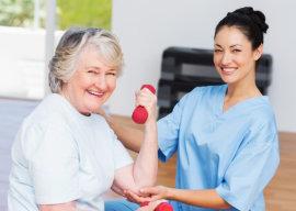 caregiver guiding a senior woman in exercising