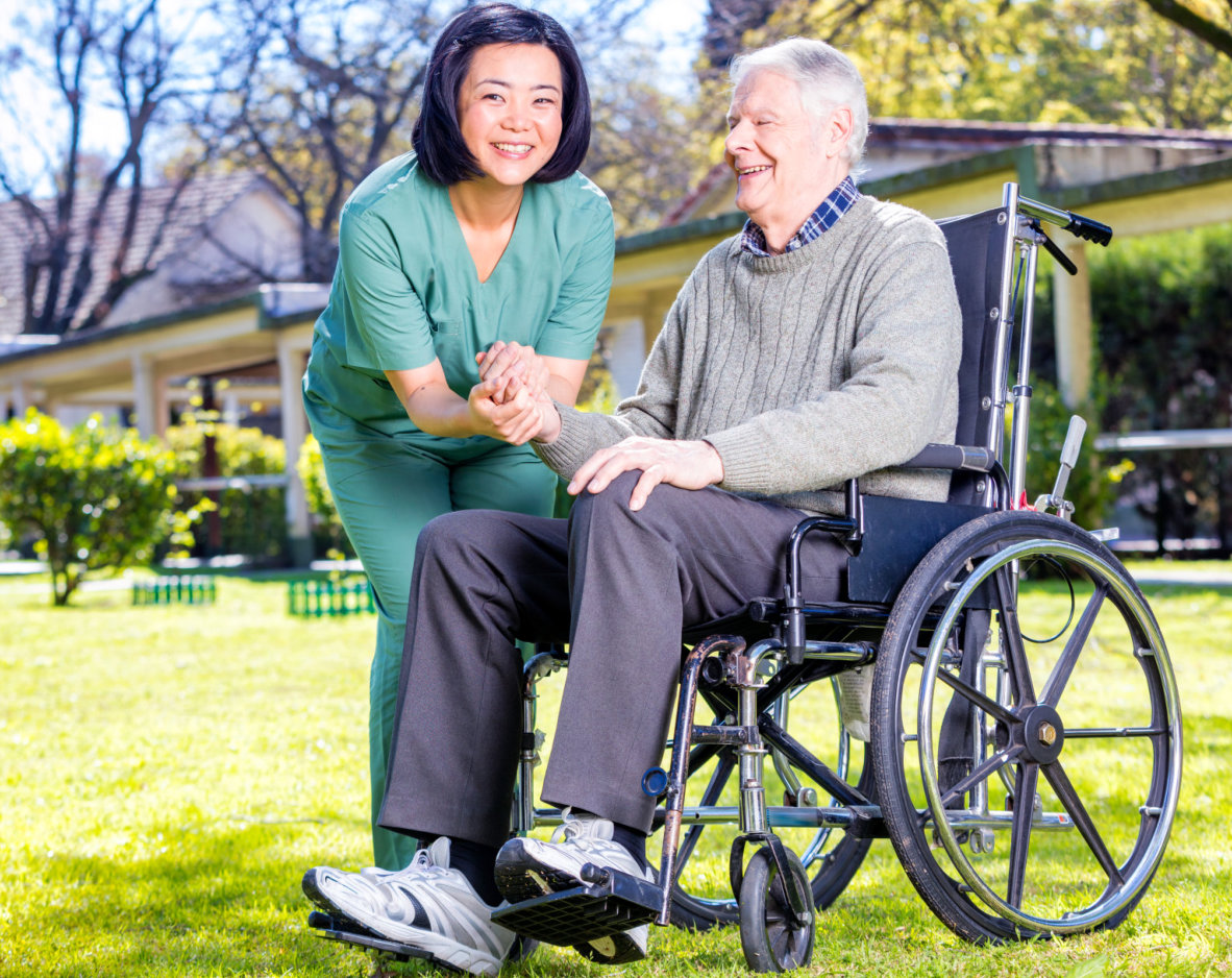caregiver holding the hand of senior man