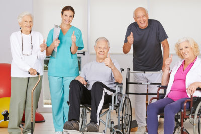 therapist with senior men and women doing thumbs up