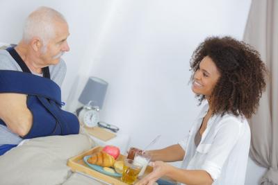 woman serving food to injured senior man