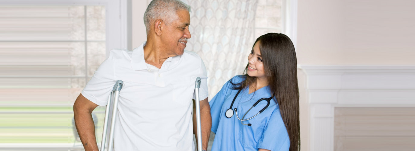 nurse and senior man smiling at each other