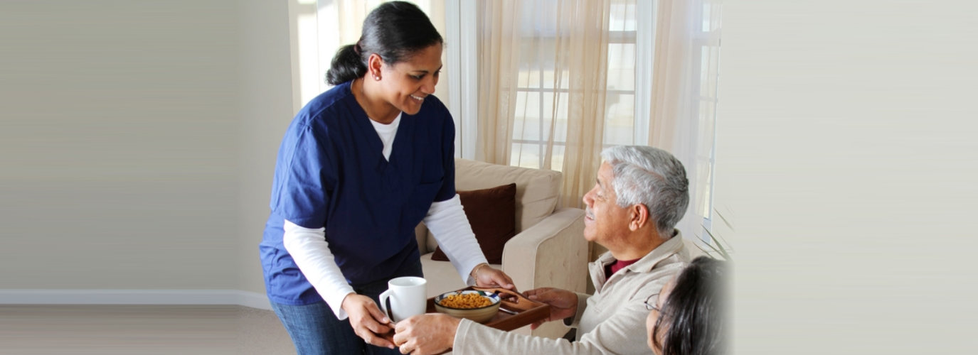 caregiver preparing food for senior man and woman