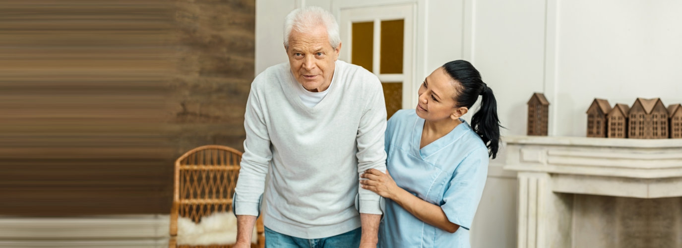 caregiver guiding senior man to walk